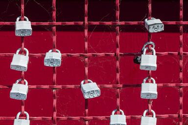 Grey padlocks affixed to a red metal grid fence