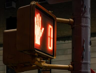 A crosswalk sign at red with a hand indicating 'do not cross'