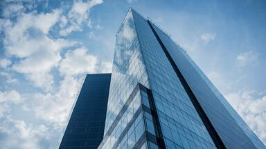 Low angle photo of a glass-fronted high-rise building